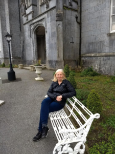 Patricia sitting on a bench in front of a stone building